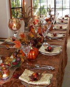 I love how this is decorated with the tall glasses, and the candles in them. This really is a nice autumn table set for a dinner party.