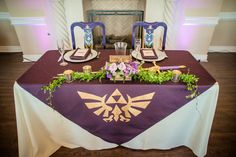 Our sweetheart table was rad. A large hand-painted purple cloth over it, Mr and Mrs goblets for our drinks, hand-painted chairs for us with the same design as our banners over the ceremony, complete with Zelda's sword from Twilight Princess.  https://www.etsy.com/listing/182141561/etched-legend-of-zelda-inspired  http://www.replicadungeon.com/princess-zelda-sword.html