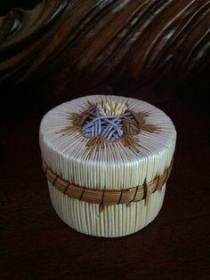 An Ojibway porcupine quill box made of porcupine quills, birchbark and sweet grass .