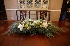 This long and low centerpiece was designed for a neutral, understated interior. I was inspired by a woodland theme and fell in love with the Carolina Blue Cypress evergreen branches at my floral wholesaler. The scabiosa pods and pine cones further carry out the wintry look accenting the snowy white flowers of majolika spray roses and Star of Bethlehem, and the green ruffle super green roses to signify rebirth. #how do you holiday?