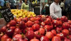 Israelis walking past a shop selling pomegranates in Mahaneh Yehuda Market in central Jerusalem. Photo by Reuters