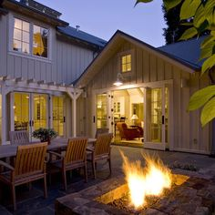 What a backyard patio! Love the built-in firepit, vertical siding, french doors & pergola!