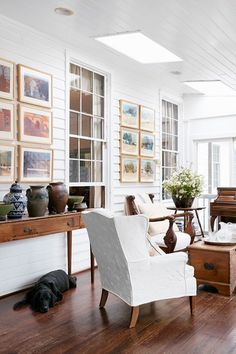 Panelled conservatory living room with white walls and dark wood floor, antique…