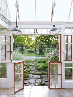 The glass house, used for entertaining and as guest quarters, opens onto a limestone path and cutting garden. Brown crafted the bifold doors out of old windows and customized the vintage-iron pendants with paper Pottery Barn shades and wire lampshade frames.    Read more: Backyard Garden Ideas - Kentucky Home and Garden - Country Living