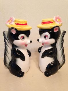 """This cheerful set of shakers are in wonderful condition with no cracks, chips, crazing or paint loss. What looks like paint loss on the ears is actually just lack of paint - the areas are under glaze. The set looks as though it was only used for display. Stoppers are in great condition. One figure retains the Norcrest Japan original label. The figures are 3 7/8"""" high. 