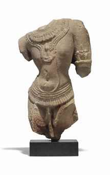 A SANDSTONE MALE TORSO CENTRAL INDIA, 12TH CENTURY Carved in tribhanga, wearing a dhoti secured around the waist with a beaded belt, wearing necklaces and an armlet, on stand 18 1/8 in. (46 cm.) high
