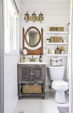 Masterbath inspiration. Resurfacing the pink tile with pure white, replace sink with smaller vanity, remove all the towel bars, paint the walls pale grey, install floating shelves above toilet, install towel hooks across from toilet, replace mirror with bigger one, update light fixture.