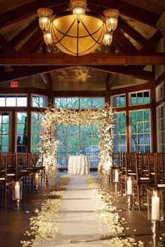Wooden indoor setting, floral arch, wooden chairs, petal-lined aisle, big windows as backdrop.