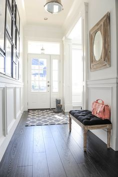 Light hallway with dark wood floors - The Doctor's Closet Home Tour photographed by Tracey Ayton Gray tufted bench in white foyer with dark wood floors Decor, Home, House Styles, Finding A House, Interior, New Homes, House, House Interior, White Decor