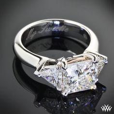 The center diamond is a 2.058ct A CUT ABOVE® Princess which is flanked with two 0.35ct Trillion Cut Diamonds. This custom 3 Stone Diamond Engagement Ring is set in Platinum with Rose Gold accents.