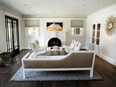 Dark Brown Laminated Wooden Floor Grey Fur Rug White Wall With Ornament White Fireplace And White
