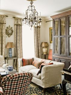 Robert Kime ~ In the city, the Downland sofa and Belgian linen curtains in the sitting room are from Kime's own line and the rug is late-19th-century William Morris.