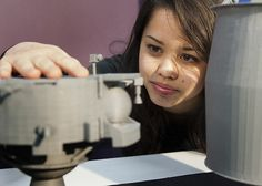 Team member Kara Morgan (Penn State aerospace engineering freshman) examines a 3-D printed model of Lunar Lion spacecraft.