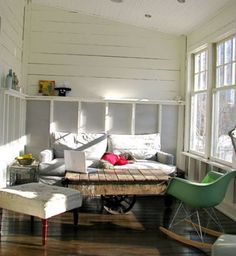 inspiration for sunroom! this is sparse but i like the elements of couch, chairs, footstool, large cofee table and lots of light!
