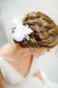 This bride chose a feather hair accessory for her chic nature-inspired wedding.    Photography courtesy of Nancy Da Costa from Mango Studios.