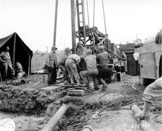 American soldiers in a deposit of material in the open. Unloading a Chevrolet G-7113 tractor with trailer 3.5t stake and plateform. Report on the construction site of the 5th General Hospital in late July 1944 to Carentan.