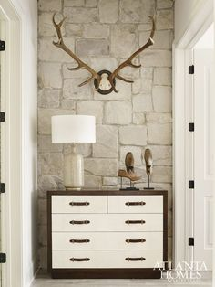 Gorgeous hallway detail.  The rustic stone and antlers with a classic dresser works beautifully.