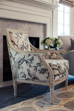 great looking large print, black & white fabric chair in front of grey, marble fireplace