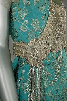 A turquoise and gold brocaded satin evening gown, circa 1917, un-labelled, the bodice adorned with tasselled panel of silver bugle beads, tulle sleeves, above draped skirt with wide inner petersham waistband. Detail by Skylar Seed