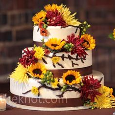 Fresh sunflowers, spider mums and berries, along with branch-inspired piping, cascaded down the cake.