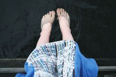 Feet in the water and knees wrapped in a towel poncho.