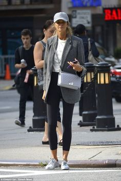 Fresh faced: Macpherson wore an oversized checked blazer, simple black leggings and a slogan tee, which she tucked into her tight bottoms