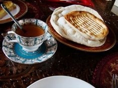 """""""A cup of hot fragrant kehwa (Kashmiri green tea, brewed with cardamom and cassia), served with Kashmiri breads - the chewy golden girda, and the soft, thin lavasa."""" by phileasfogg."""