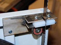 Bandsaw Blade Guide by John Heisz -- Homemade bandsaw blade guide constructed from  flat bar stock, UHMW plastic, bearings, and screws. http://www.homemadetools.net/homemade-bandsaw-blade-guide-5