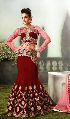 Let the air of mystery and enchantment linger as you step out in this maroon embroidered velvet fish cut style lehenga choli. This enticing dress is showing some extraordinary embroidery done with jaal, resham and stones work. #DazzlingRedLehengaCholi