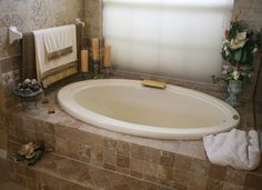 Earthtone bathroom with dark brown tile & decorative wallpaper - Towels & candles as stunning Accents