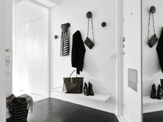 czarna posadzka,druciany koszyk,wisząca półka i czarne grzybki-wieszaki w białym korytarzu