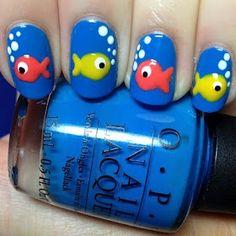 Pink and yellow fish nails on bright blue nails.