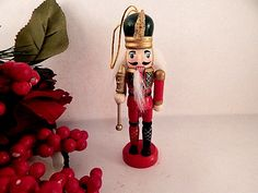 "Nutcracker Soldier Christmas Tree Ornament 1980's Hand Painted Wooden Figurine Traditional German style nutcracker style figurine with moving lever jaw Flat base allows use as a figurine 5 1/4"" h x 2"" l x 1 1/4"" w 2"" gold cord hanging loop A ..."