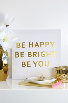 """Every sunny day starts with a happy little reminder like the Be Happy White and Gold Wall Canvas! A chic white canvas has gold foil lettering that reads """"Be Happy. Be Bright. Be You."""". Wooden frame has a built-in hold for easy hanging."""