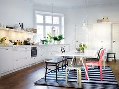 white kitchen with colour accented chairs