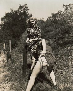 """I'll go first."" Vintage photo of two women climbing through barbed wire fence."