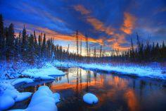 The setting sun illuminates the water of Hazel Creek near the village of Teslin, Yukon Territory.