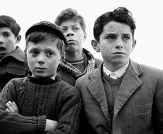 I bambini che si sfidano al tiro alla fune in piazza e i contadini che rientrano dai campi curvi sotto il peso dell'ennesima giornata di lavoro. Ma anche i sorrisi delle sagre di paese, la calma degli anziani seduti sui gradini fuori da una chiesa e i desideri di cambiamento e rinascita propri del b