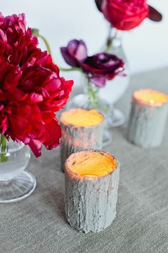 Concrete votives. I wonder if you could reuse the mold, instead of using multiple glass votives.