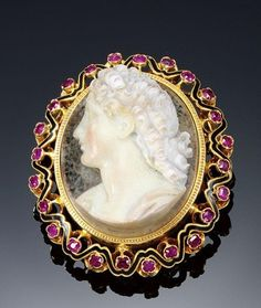 GOLD, ENAMEL, RUBY AND HARD STONE BROOCH/ PENDANT. The central hard stone cameo carved to depict the dextral profile of a lady, within a border of circular-cut and cushion-shaped rubies embellished with interlaced  black enamel detail.