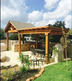 Photo of Backyard Paradise - Magnolia, TX, United States. Rough cedar gable roof patio cover with exposed cedar ceiling and attached rough cedar pergola