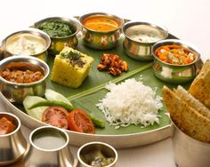 Thali - a large plate with various Indian foods from Gujarat. With 22,464 delicacies from the states of Gujarat and Rajasthan alone, the possibilities of Indian food are endless. This is typical food eaten for lunch or dinner in India. It could consist of 4 types of shaak made with potatoes, okra, beans, chickpeas etc, raita - indian yogurt, pickles, lentils, vegetables, paratha (flaked indian bread), Daal (spicy indian lentil soup), Indian sweet (mithai) and is one of the most healthiest…