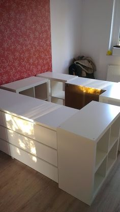 Example of elevated platform bed with under bed storage.   Add a mattress platform on hinged wall mount to access the hidden storage space between cabinet surround.   Japanese futon mattress on platform (cleanable and airable, unlike traditional American mattresses).