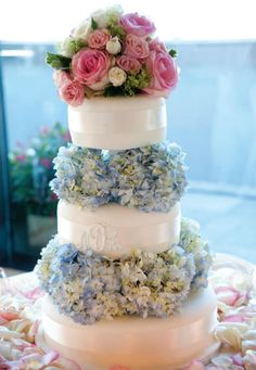 Romantic white three tier cake with blue hydrangea trim and pink rose bouquet topper.