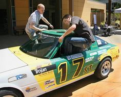 Cal Poly students climbing into Cal Poly's Electric Race Car.