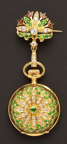 Edwardian Lady's 18kt Gold, Demantoid Garnet, Enamel, and Diamond Pendant Watch, Tiffany & Co., the white enamel dial with Arabic numeral indicators, jeweled nickel movement no. 11752, set throughout with circular-cut demantoid garnets and old European-cut diamond melee, red enamel highlights, 24 mm, suspended from a conforming watch pin, total lg. 2 3/8 in., case nos. 11752, 270, signed movement, dial, case, and watch pin.