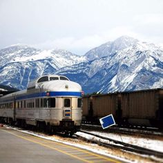 a train is parked on the side of a snow covered mountain: This Spectacular 4-Night Train Trip Across Canada Only Costs $431!