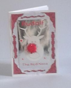 """Children's Christmas RUDOLF card. £1.50 + P&P. There is a background patterned paper and a white oval shape with a fancy edge around it and more smaller shaped pieces in the matching background paper to enhance the design. There is a central picture in silver with a reindeer head in white, and he has a sparkly red pompom nose. At the top is his name Rudolf. This is a fun card and is 6"""" x 4"""". There is a blank white insert for you to add a  message inside and it comes with a white envelope."""