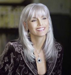 Emmylou Harris' trademark gray hair is a flashy shade of bright silver, which she keeps youthful with an up-to-date ' do that frames her pretty face with bangs and layers. Description from pinterest.com. I searched for this on bing.com/images