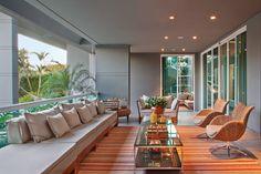 A varanda integrada ao social conta com estar, mesa de refeições e bancada de apoio em frente à cozinha gourmet.
